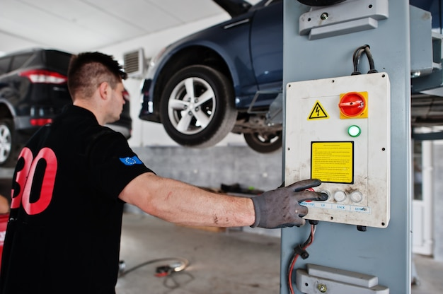 Car repair and maintenance theme. mechanic in uniform working in auto service, press button to lifting auto.