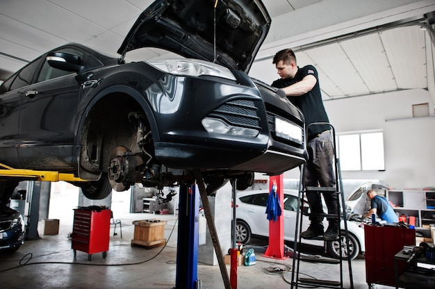 Car repair and maintenance theme. mechanic in uniform working in auto service.