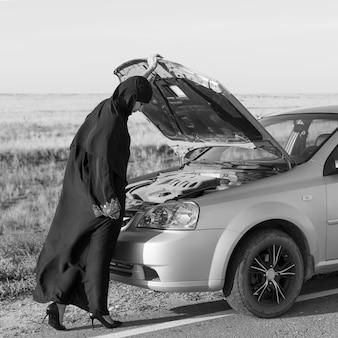 Ремонт автомобилей в дороге. женщина-водитель у капота. черное и белое