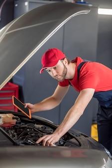 自動車修理。ガレージのボンネットの下で車を調べるタブレットを備えたキャップとオーバーオールの真剣で気配りのある自動車整備士