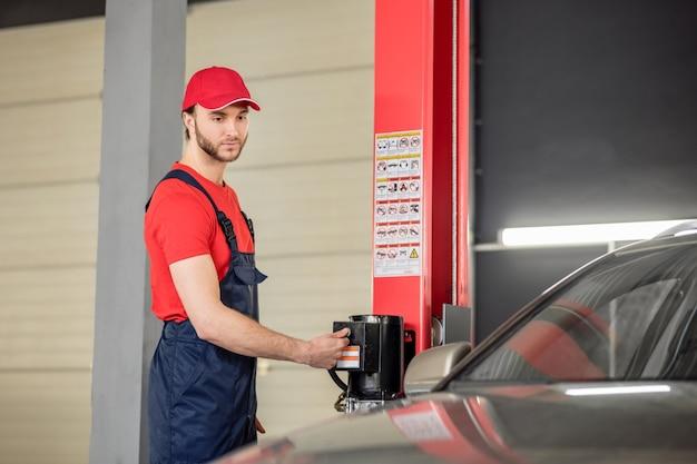 車の修理店。仕事のオーバーオールと車のワークショップで特別なデバイスのキャップを押すボタンの深刻な若い成人男性
