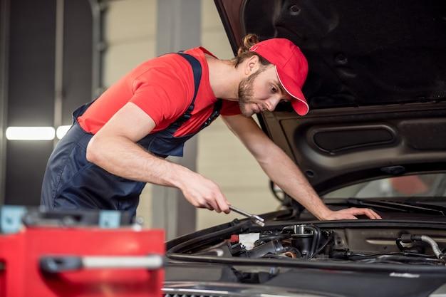自動車修理。ワークショップで車のボンネットの近くでレンチを曲げたオーバーオールの若い大人の真面目な男