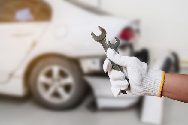 자동차 수리 배경, rapair 차고에서 흐림 깨진 자동차와 차고에서 일하는 렌치와 자동차 정비사의 손.