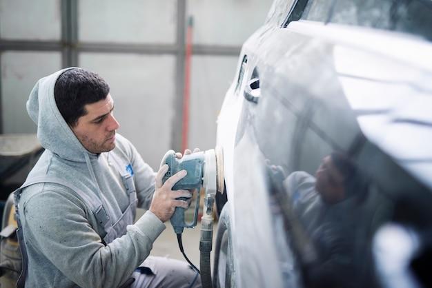 자동차 수리공은 차체를 연마하고 새 페인트를 위해 차량을 준비합니다.