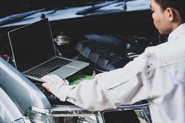 Car repairman wearing a white uniform standing and holding a wrench that is an essential tool for a mechanic with laptop checking engine