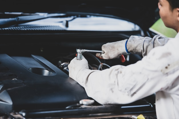Car repairman wearing a white uniform standing and holding a wrench that is an essential tool for a mechanic