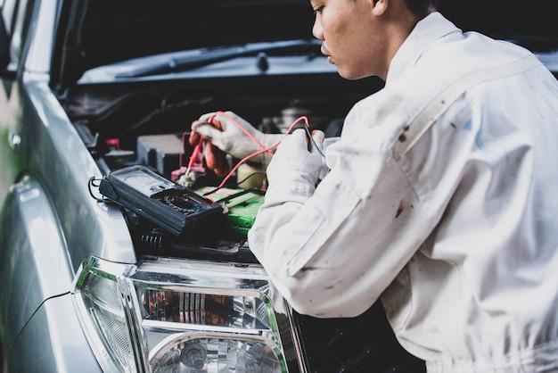 Riparatore di auto che indossa una divisa bianca in piedi e in possesso di una chiave che è uno strumento essenziale per un meccanico