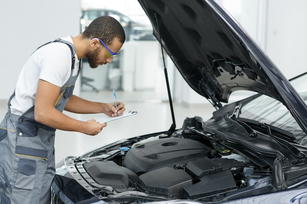 Car repairman writing on his clipboard while working at the garage
