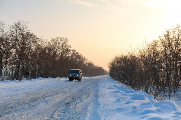The car rides on a snowy highway. difficult weather conditions.