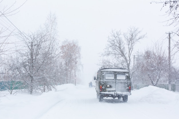 The car rides on a snowy highway. difficult weather conditions