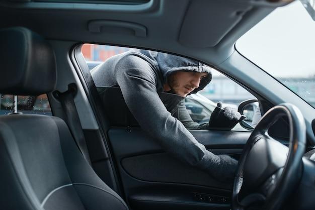 Автомобиль грабитель открывает дверь, рискованная работа, угон. бандит в капюшоне садится в машину на стоянке. автомобильное ограбление, автомобильное преступление