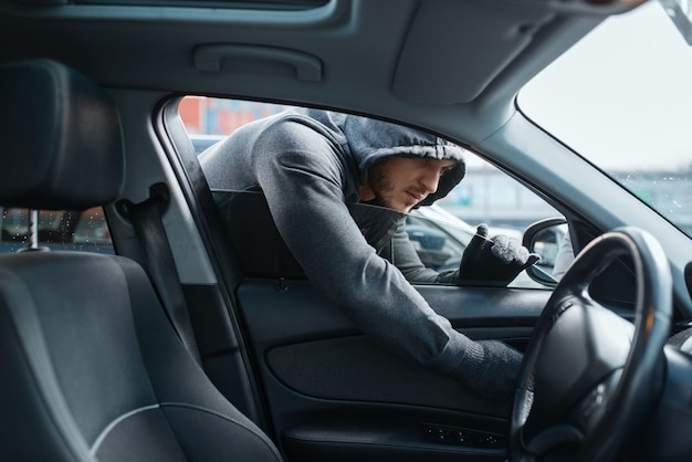 Car robber opening door, risk job, stealing. hooded male bandit gets into the vehicle on parking. auto robbery, automobile crime