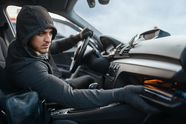 Car robber searches the glove compartment, dangerous hobby, stealing.