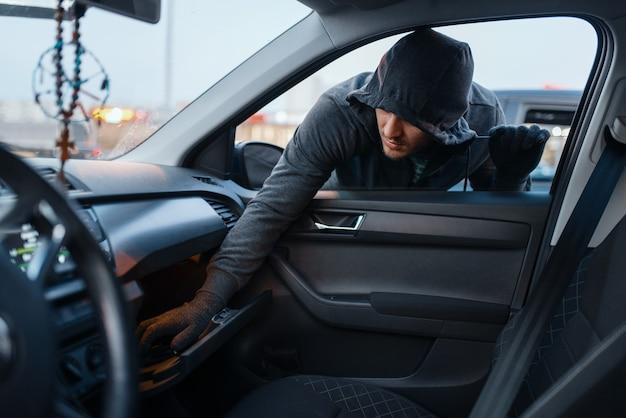 Автомобильный грабитель угоняет женскую сумочку, преступный образ жизни, угон. бандит в капюшоне открывает машину на стоянке. авто грабеж