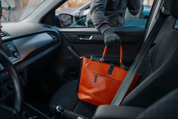Car robber steals women's handbag, criminal lifestyle, stealing. hooded male bandit opening vehicle on parking. auto robbery, automobile crime