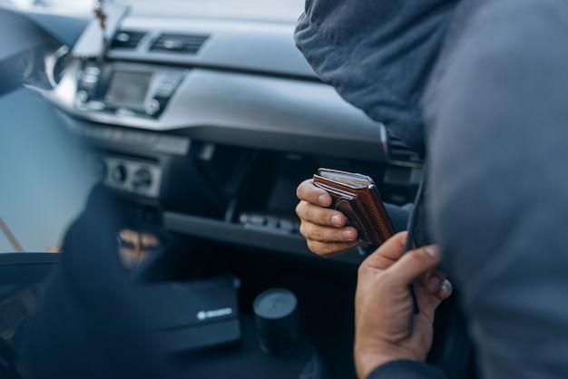 Автомобильный грабитель забирает кошелек из бардачка, преступный образ жизни, угон. бандит в капюшоне открывает машину на стоянке. автомобильное ограбление, автомобильное преступление