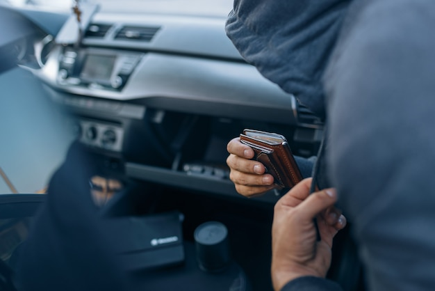 Car robber takes the wallet from the glove compartment, criminal lifestyle, stealing. hooded male bandit opening vehicle on parking. auto robbery, automobile crime