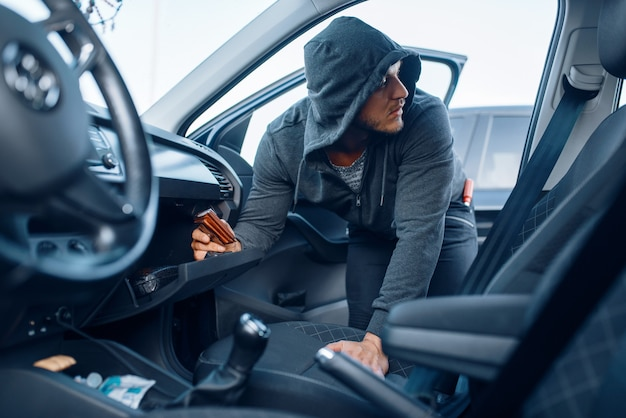 Car robber takes the wallet from the glove compartment, criminal lifestyle, stealing. hooded male bandit opening vehicle on parking. auto robbery