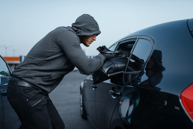 Car robber takes women's handbag, criminal lifestyle, stealing. hooded male bandit opening vehicle on parking. auto robbery, automobile crime