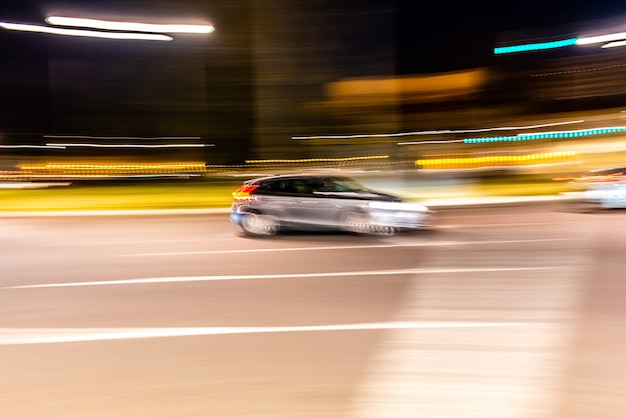Car rolling at full speed through the city at night