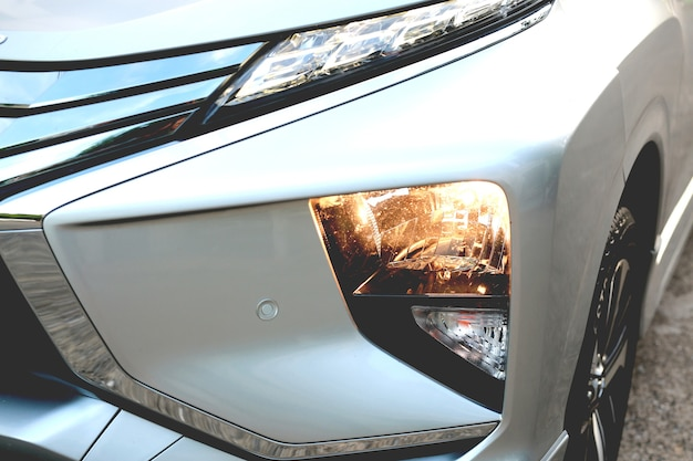The car's light is on. close. turn on the car's headlights. b