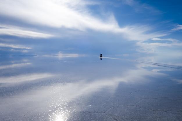 Car in salar de uyuni salt flats desert, andes altiplano, bolivia