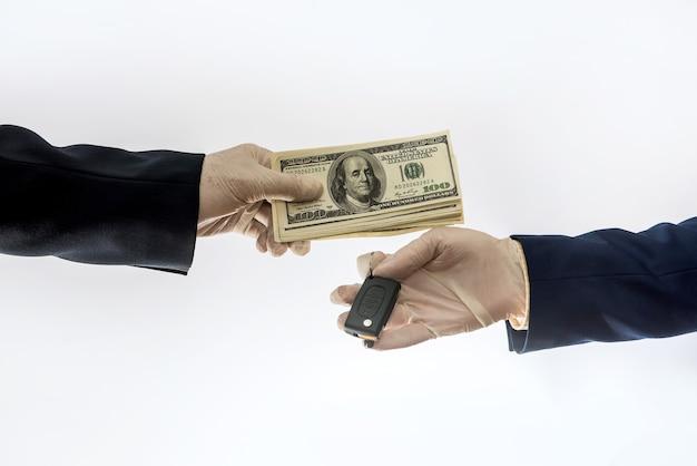 Продажа автомобилей в условиях карантина, руки из-за коронавируса держат ключ от машины и долларовые купюры изолированы. покупка автомобиля концепт