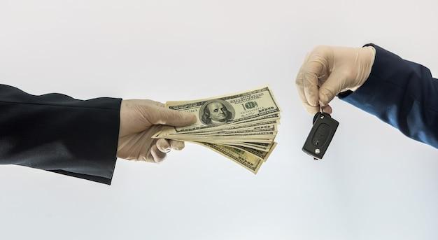 検疫条件での自動車販売コロナウイルスの手が車のキーとドル紙幣を保持している。車のコンセプトを購入する