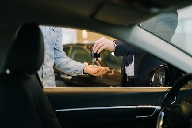 Продавец автомобилей передает ключи от новой машины молодому покупателю-мужчине в автосалоне