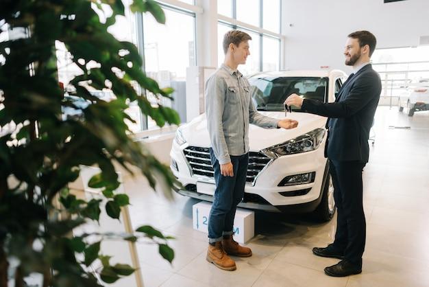 Продавец автомобилей передает ключи от нового автомобиля покупателю молодого человека в автосалоне перед автомобилем
