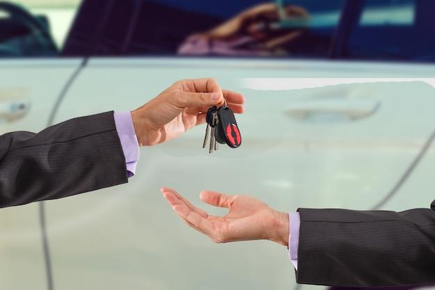 Продавец автомобилей передает ключи от новой машины молодому бизнесмену