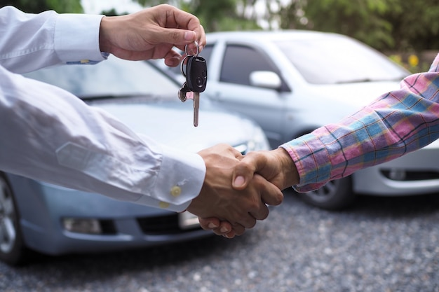 The car salesman is handing over the keys to the buyer after the lease has been agreed.