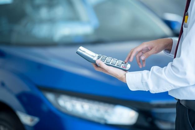 車のショールームでビジネスファイナンスの車のセールスマンを押す電卓新しい青い車ぼやけて背景。