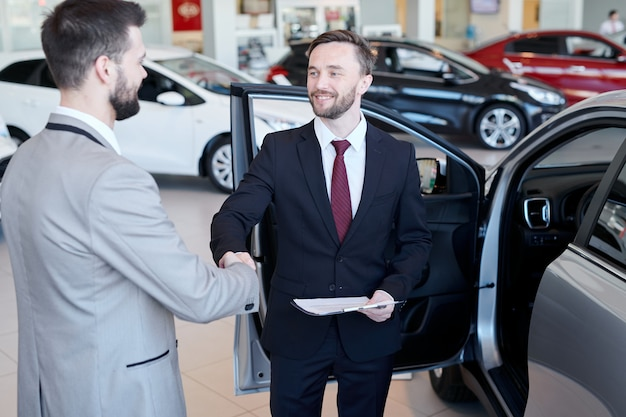 Car salesman shaking hands with client