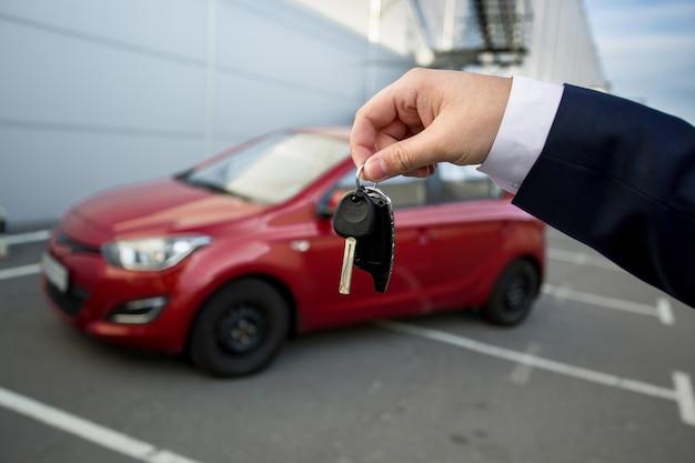 新車のリモートアラーム付きのキーを示す車のセールスマン