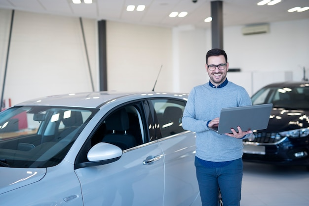 Car salesman with laptop computer standing in front of new vehicle at dealership showroom.