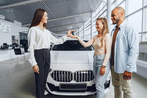 Продавщица автомобилей в автосалоне разговаривает с покупателями клиентов