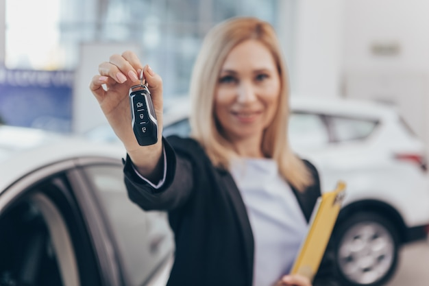 Car saleswoman smiling cheerfully holding out car key to the camera