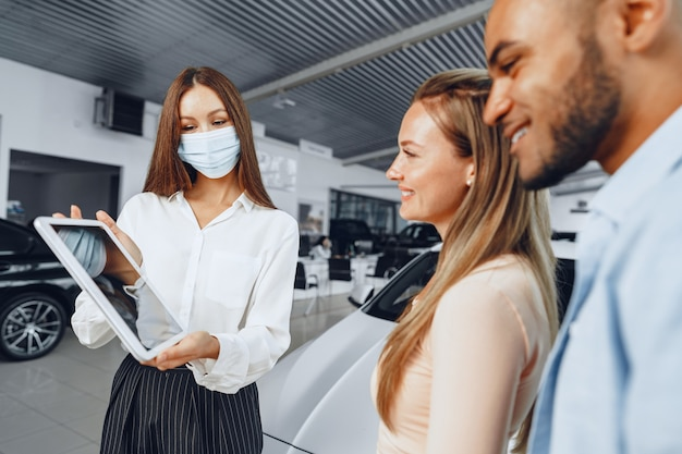 Car saleswoman wearing medical mask shows buyers couple something on digital tablet. .new pandemic job requirements concept