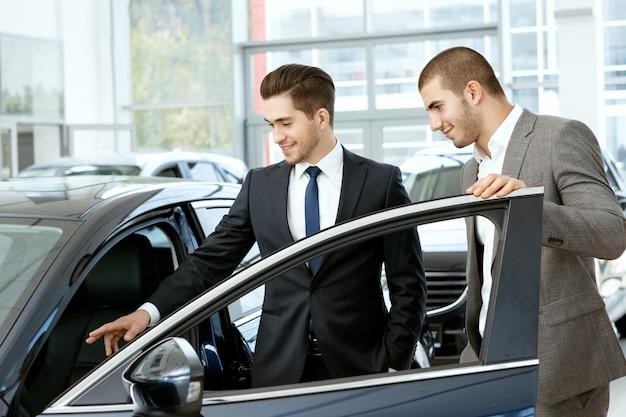 カーサロンマネージャーが車の中で見てみるように青年実業家クライアントを招待