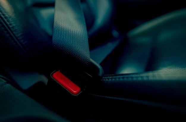 赤い押しボタン付きのカーシートベルト。安全とセキュリティのためにシートベルトを締めて、自動車事故から生命を守ってください。