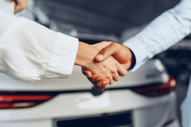 車の売り手と買い手が車に対して握手する