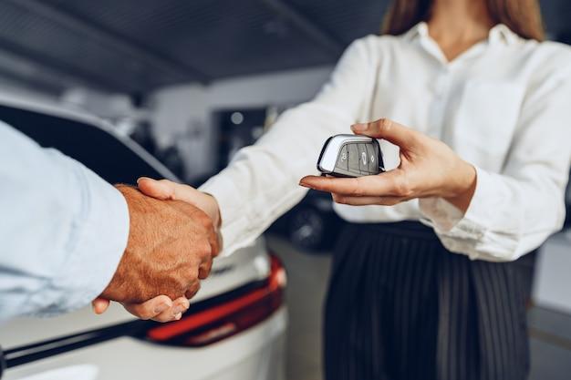 新しい車の背景に対する自動車販売店での自動車の売り手と買い手の握手