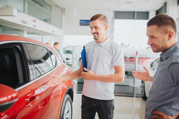 자동차 판매자와 고객은 아름다운 빨간 차에 서서 그것을 봅니다.