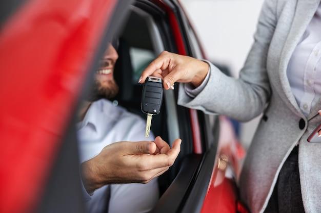 新しい車に座っている買い手に車の鍵を渡す車の売り手。カーサロンのインテリア。