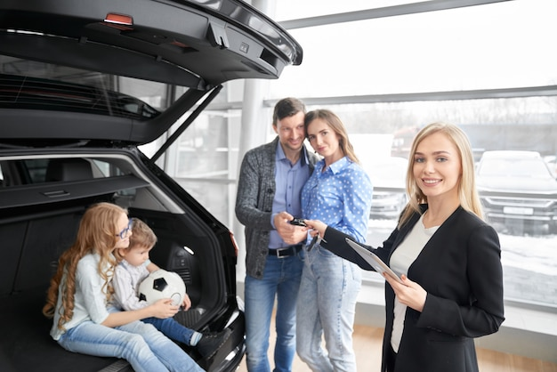 Car seller looking at camera and giving keys of car clients