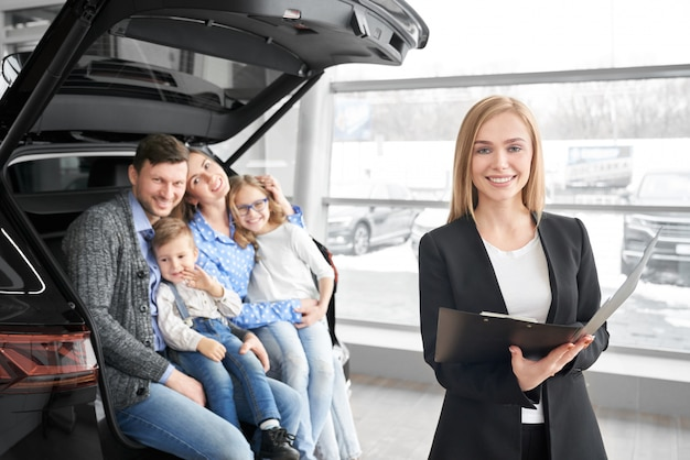 Car seller looking at camera and posing in auto showroom