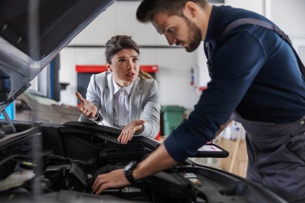 Продавец автомобилей разговаривает с механиком, ремонтирующим автомобиль