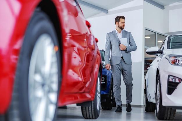 Продавец автомобилей ходит по автомобильному салону и держит планшет