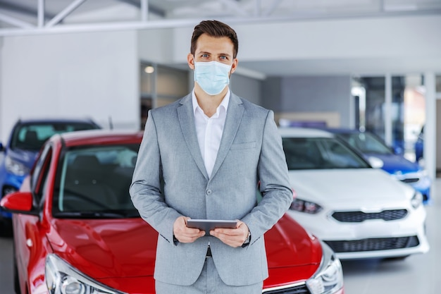 Продавец автомобилей с лицевой маской на стоя в салоне автомобиля и держа таблетку, смотря камеру. новый нормальный.